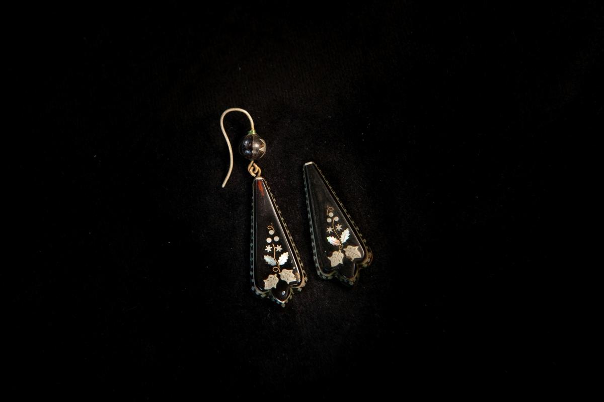 Trekantiga örhängen av brunsvart lackerad konstmassa, alternativt sköldpaddsskal, med inläggningar av silver och pärlemor i form av blad m.m. och lambrekängbård. Överst en inlagd silverstjärna i kula. Ena örhänget saknar kula och örkrok.