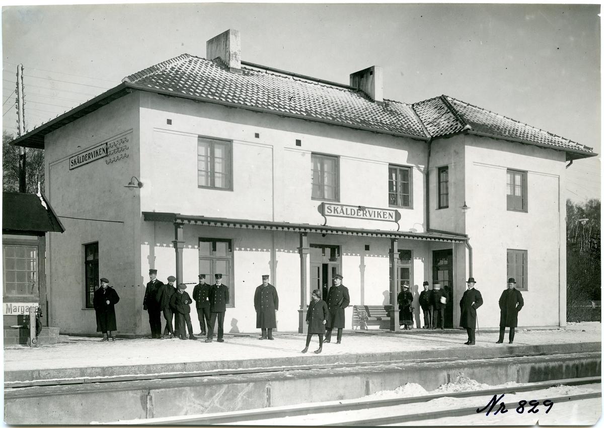 Stationshuset från tågsidan med personalen i förgrunden.