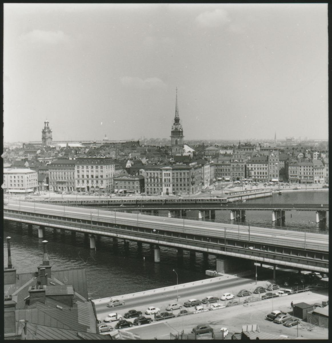 Vy över Södra delen av Riddarfjärden med Södra Mälarstrand och Södra Järnvägsbron, på sträckan Mälarstrand och Riddarholmen. Storkyrka och tyska kyrkans torn i bild. Foto taget från Basrtugatan/Pryssgränd.