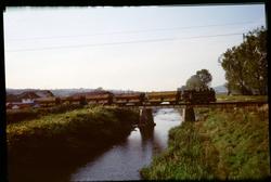 Ånglok med godsvagnar på järnvägsbro över floden Crișul Alb