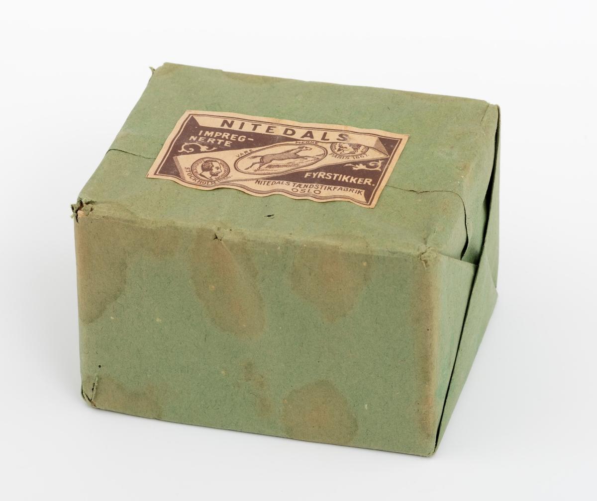 Fyrstikkesker i uåpnet pakke med en påklistret etikett. Fyrstikkeskene ligger innpakket i et grønnfarget emballasjepapir. På etiketten er det avbildet en hest og to medaljer, henholdsvis fra Stockholm i 1866 og Paris i 1867. Vi har ingen sikker datering for når denne pakken med fyrstikkesker ble  produsert.