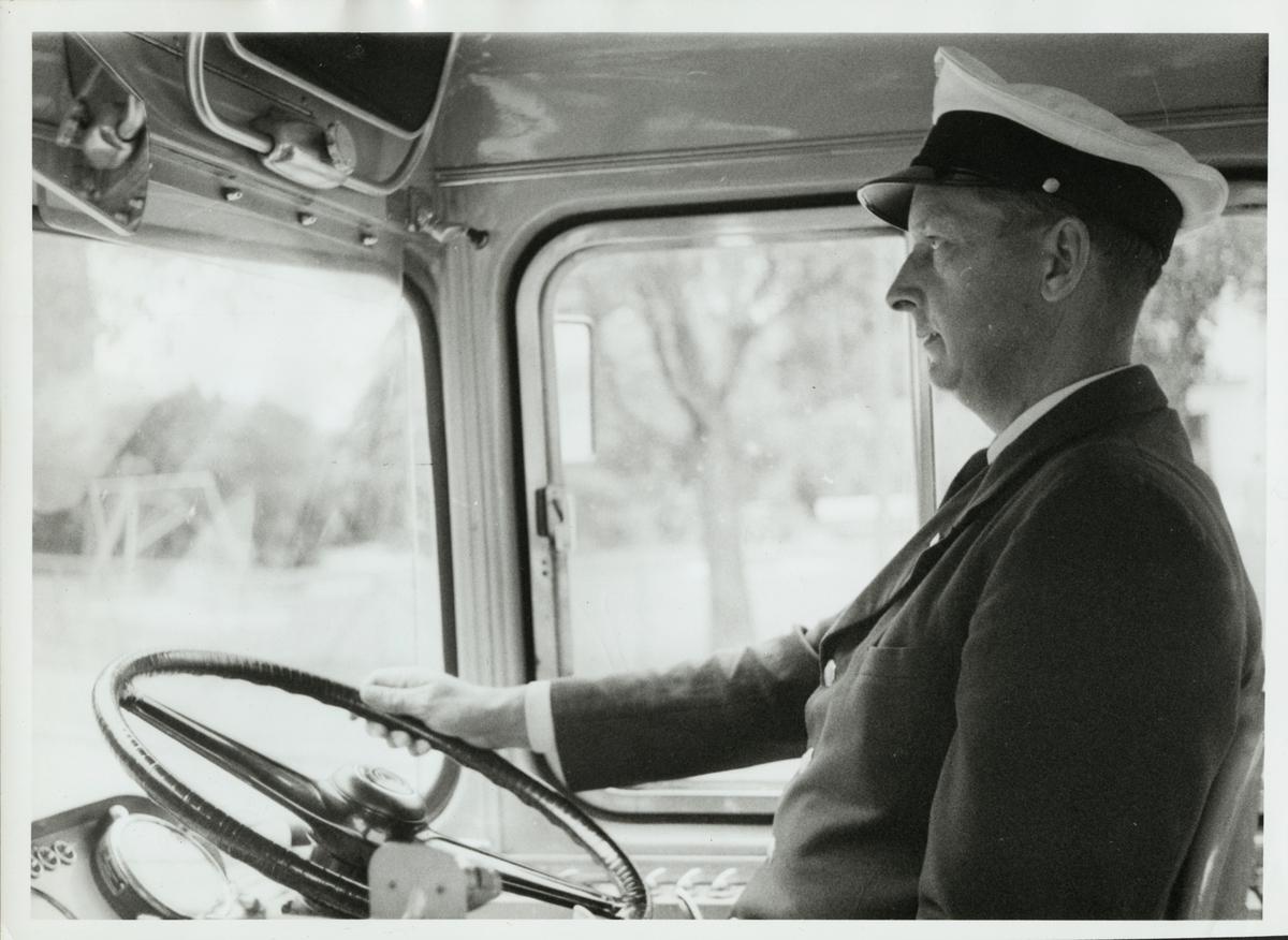Helge Lindqvist bakom ratten på en Trafikaktiebolaget Grängesberg - Oxelösunds Järnvägar, TGOJ buss.