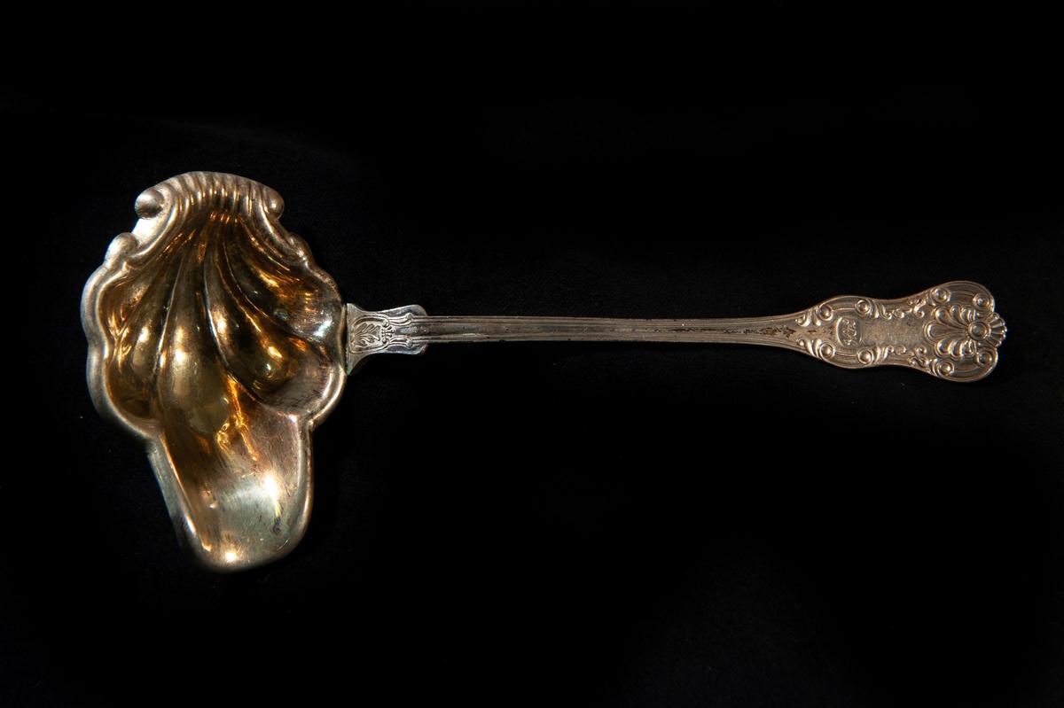 """En såssked av silver.Snäckmodell, (Queen ´s Pattern?). Förgylld skopa. Präglade initialer på skaftet: """"HCK""""."""