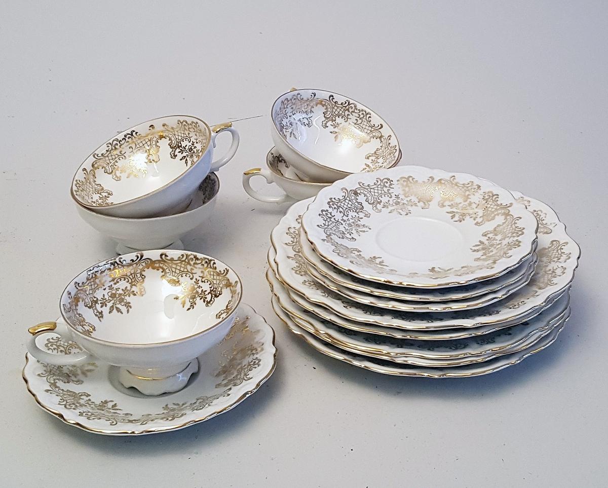 """Kaffiservise - 8 koppar, 8 tefat og 8 asjett, alle med  """"gulldekor"""" i form av stiliserte rokokko roser."""