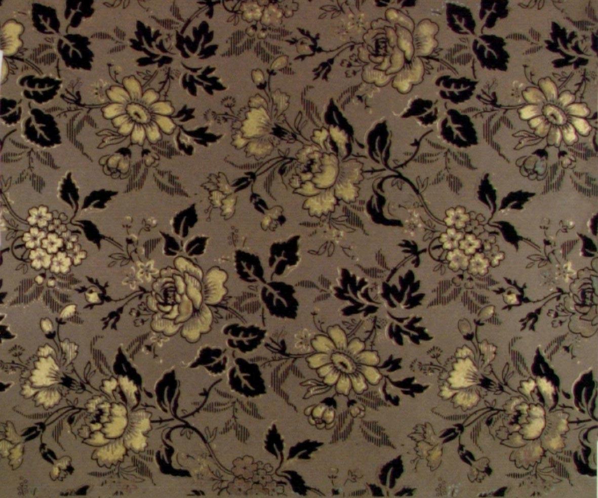 Ytfyllande blommönster i guld, svart och något turkos på ett grått genomfärgat papper. Bladen delvis sgrafferade.