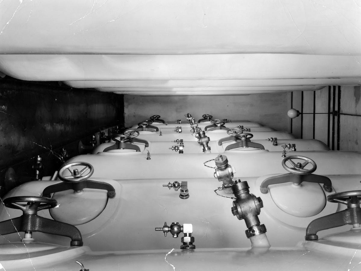 Bilden visar flera aluminiumtankar på vardera sida i bild. Fotot togs i samband med installationen av den nya jäskällaren med aluminiumtankar, köpta hos Christian Berner. De nya behållarna ersatte de gamla av trä, varför även bruket av harts försvann. Det var Eivor Bäcklunds make som, av ägaren Sten Möller, anställdes för att modernisera bryggeriet, vilket skedde i början av 1950-talet.