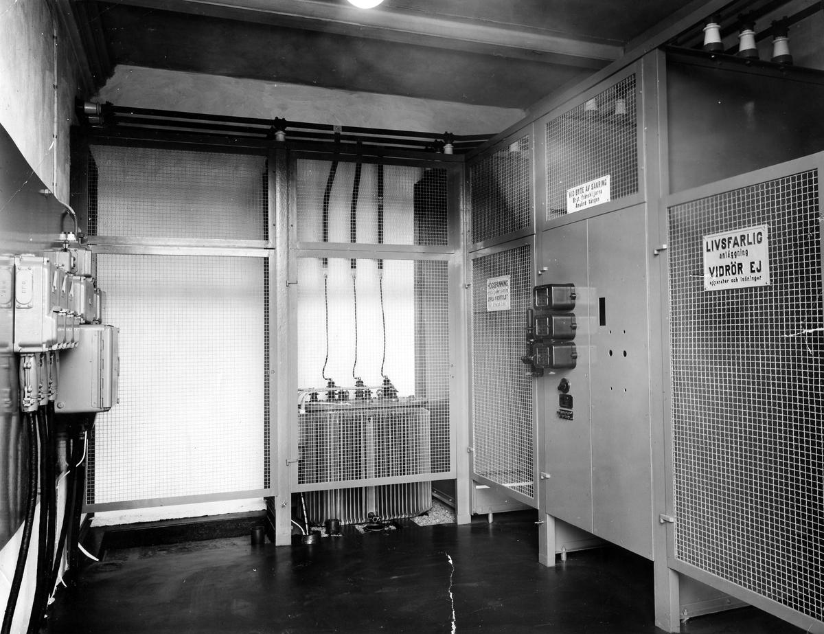 """Bilden visar den nya transformatorn, tillhöger på grinden en skylt """"Livsfarlig anläggning vidrör ej apparater och ledningar"""". Den nya transformatorn installerades i och med att bryggeriet moderniserades i början av 1950-talet. Det var Eivor Bäcklunds make som, av bryggeriägaren Sten Möller, anställdes för att modernisera bryggeriet."""