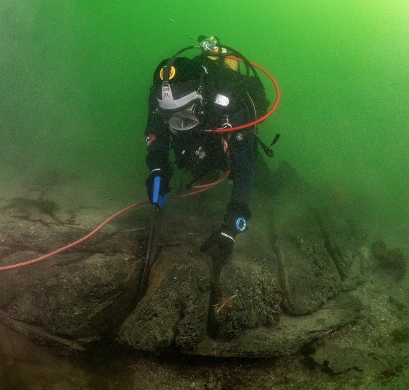 Dykker under vann sager i vrak på sjøbunnen: Arkeolog Elling Utvik Wammer sager ut skiver av hudbord til datering av skipsvraket ved Drengeholmen.