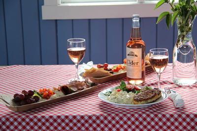 Bord pent dekket med fat med forskjellige matretter og flaske og glass med cider.