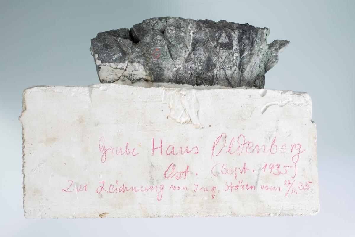 """Sølvåre i bergart, innstøpt i gips og kuttet med sag Vekt 1412,22 g Størrelse: 14 x 12 x 3 cm  Påskrift på baksiden: """"Grube Haus Oldenburg Ost (Sept. 1935) Zur Zeichnung von Ing. Stören vom 27/11 35"""