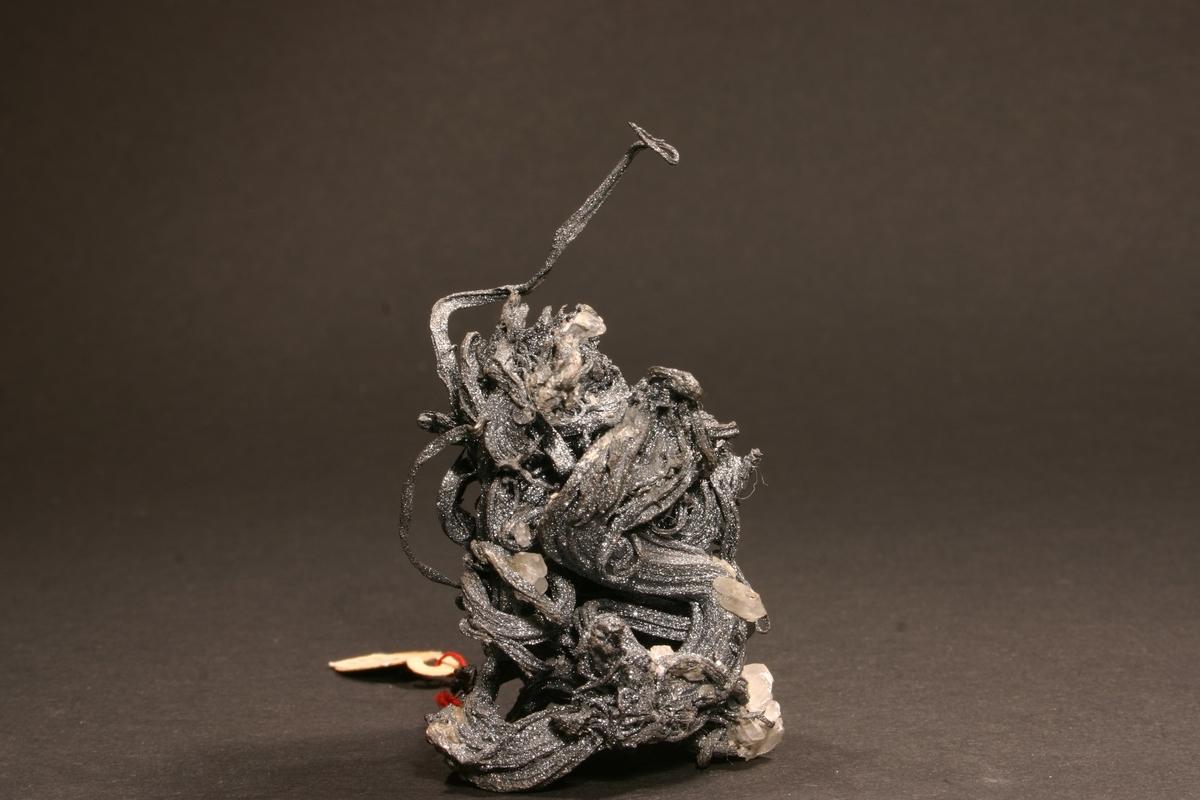 """Etikett i tråd: 305, Kongens grube Vekt 62,51 g Størrelse: 6,5 x 4 x 3,5 cm  Antagelig nr. 37 på innrammet plakat: """"37. Katalognr. 305, vekt 62 g (brutto), 50 g (sølvinnhold), Kongens, 1928. Trådsølv med tykkere blått overtrekk av krystallinsk sølvglans - sulfidert. Kalkspatt."""
