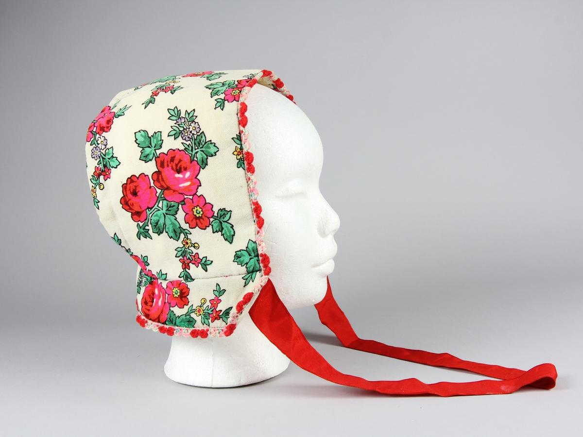 Hättas sydd av rosmönstrad ullsjal med blommor på vit botten. Fodrad med ett vitt tyg. Två delar och en veckad kant längst ner. Längs hättans ytterkanter är en frans virkad av färgat ullgarn.
