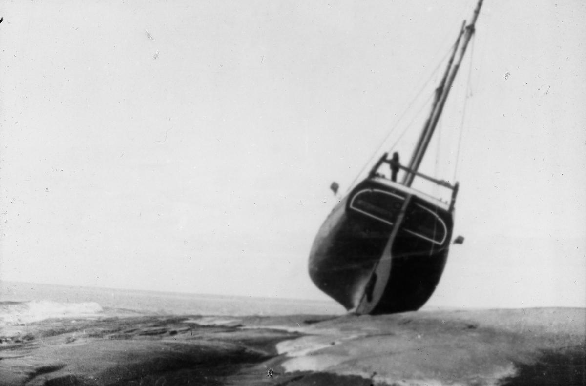Skipsvrak trukket på land på svaberg.