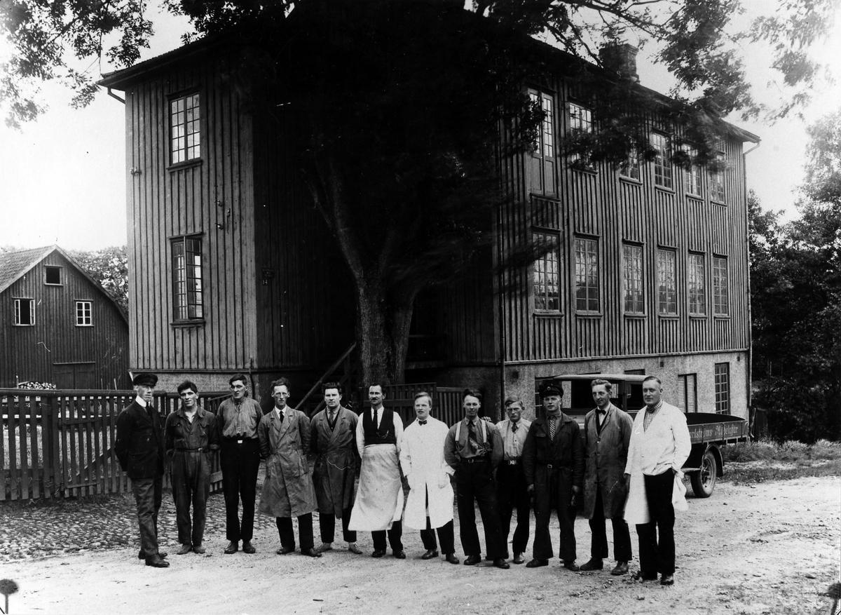 Gruppbild på personalen på Ruben Carlströms Möbelaffär framför ett trähus på 3 våningar.