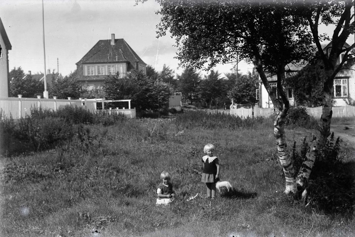 To piker med lekekatt i forgrunnen. .Motivene i Opsangers glassnegativer ble brukt som postkort. .Nedre Torfæus gate i dag ..Glassnegativ fra Bokhandler K. Opsanger.