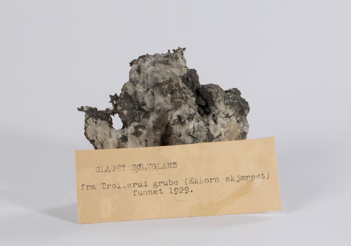 Vekt: 488,96 g To etiketter på prøve: 76 og 124 Etikett i eske: BLADET SØLVGLANS fra Trollerud grube (Ekkorn skjærpet) funnet 1929.