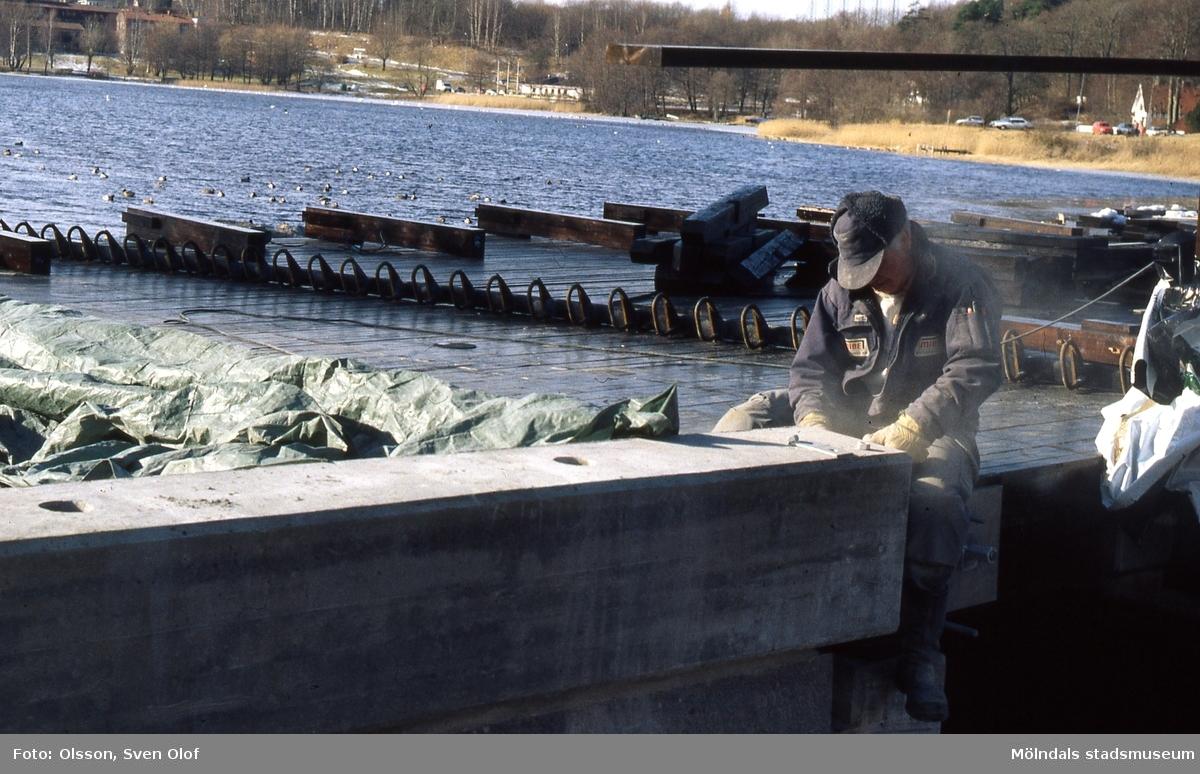 Gunnebobro vid Stensjön i Mölndal under byggnation. En byggnadsarbetare sitter på konstruktionen och arbetar den 25 februari 1999. D 31:4.