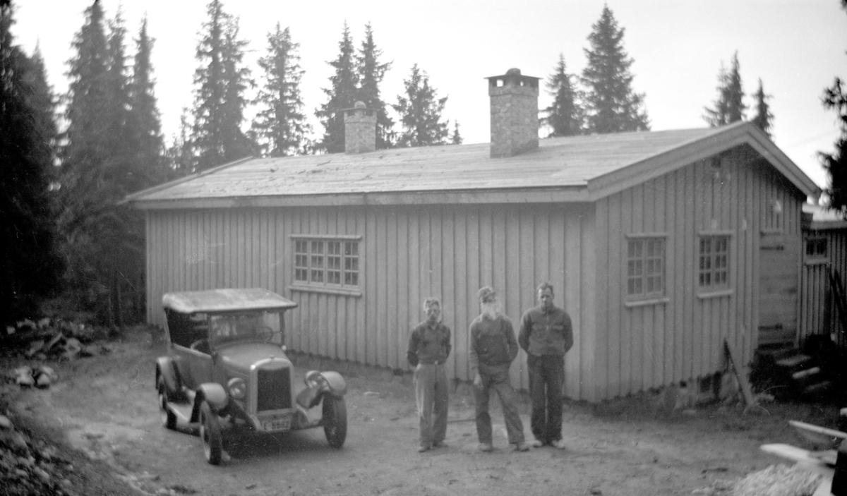 Nybygd hytte med tre mann og en bil (E-5682?) foran