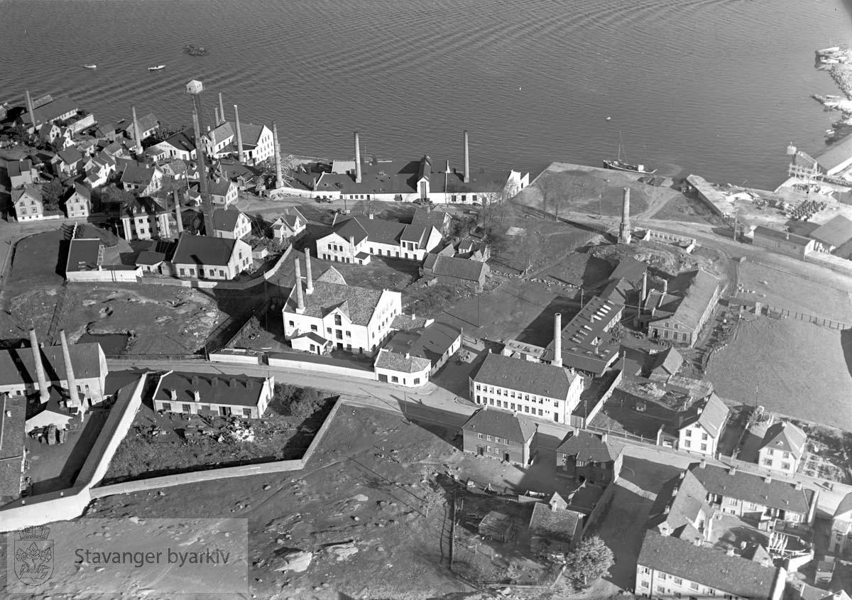 Hetlandsmarken. Mot nordøst..Oversea Canning Co...I forgrunnen: Steinhagen med kommunale arb. boliger..Videre Stavanger Tinnfabrikk med hagltårnet / haggeltårnet...Gateløp: Haugesundsgata, Rennesøygata, Ryfylkegata, Lervigsveien, Lervig, Siriskjeret..I sjøen: Siriskjær..Gamle navn: Finnøygaten, Varhauggaten, Boregaten, Hodnegaten.....