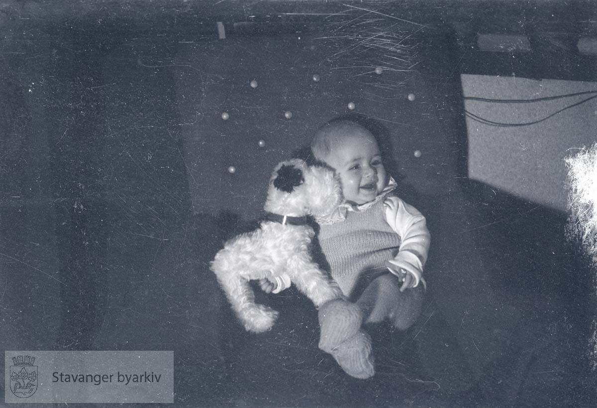Baby med kosedyr i stol.
