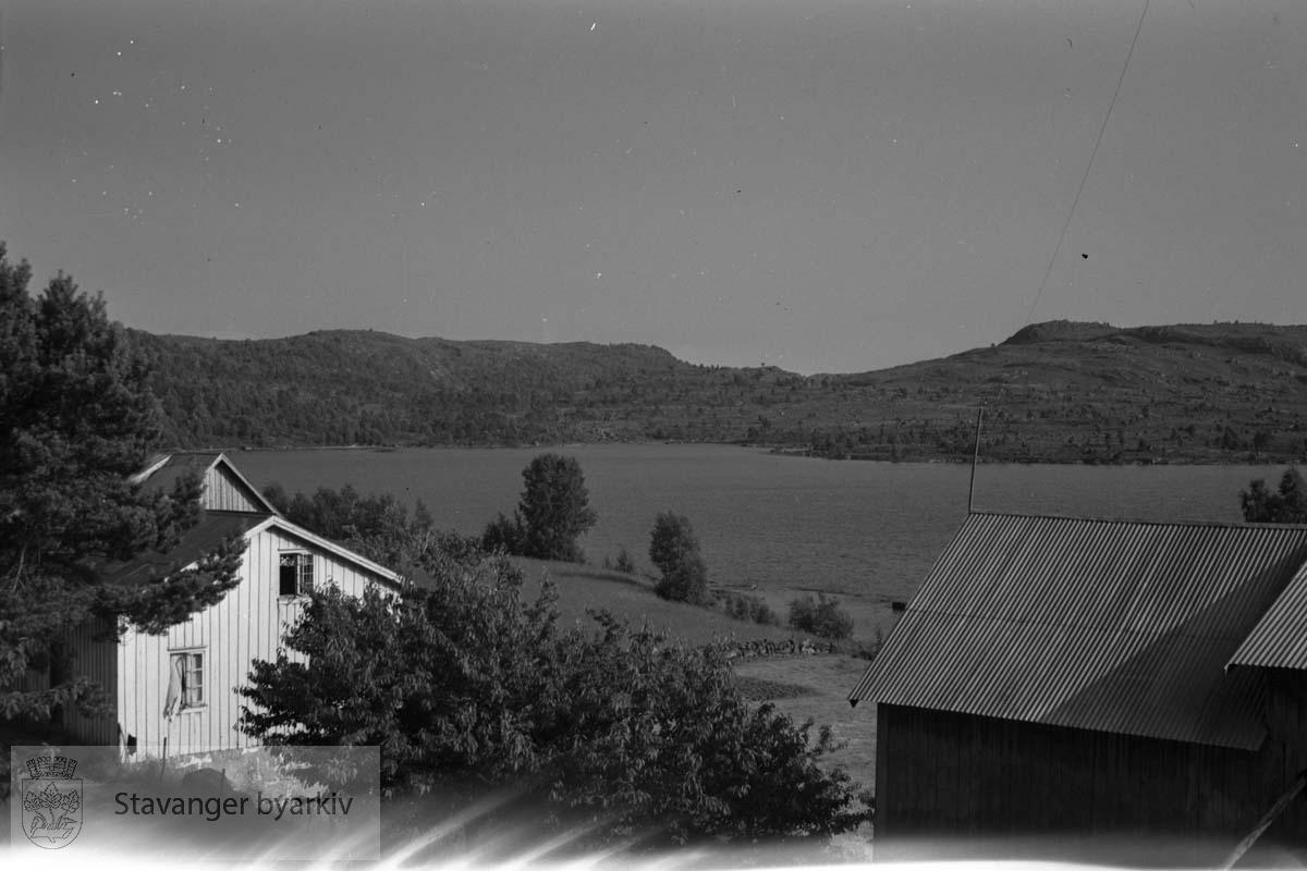 Vånigshus og låve med vann og fjell i bakgrunnen...Konvolutt merket S. Hommerstad.