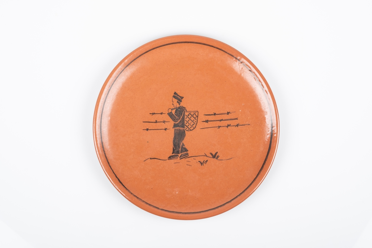 Motiv av en mannlig fange som bærer på en flettet kurv på ryggen. Han går ved piggtrådgjerdet.