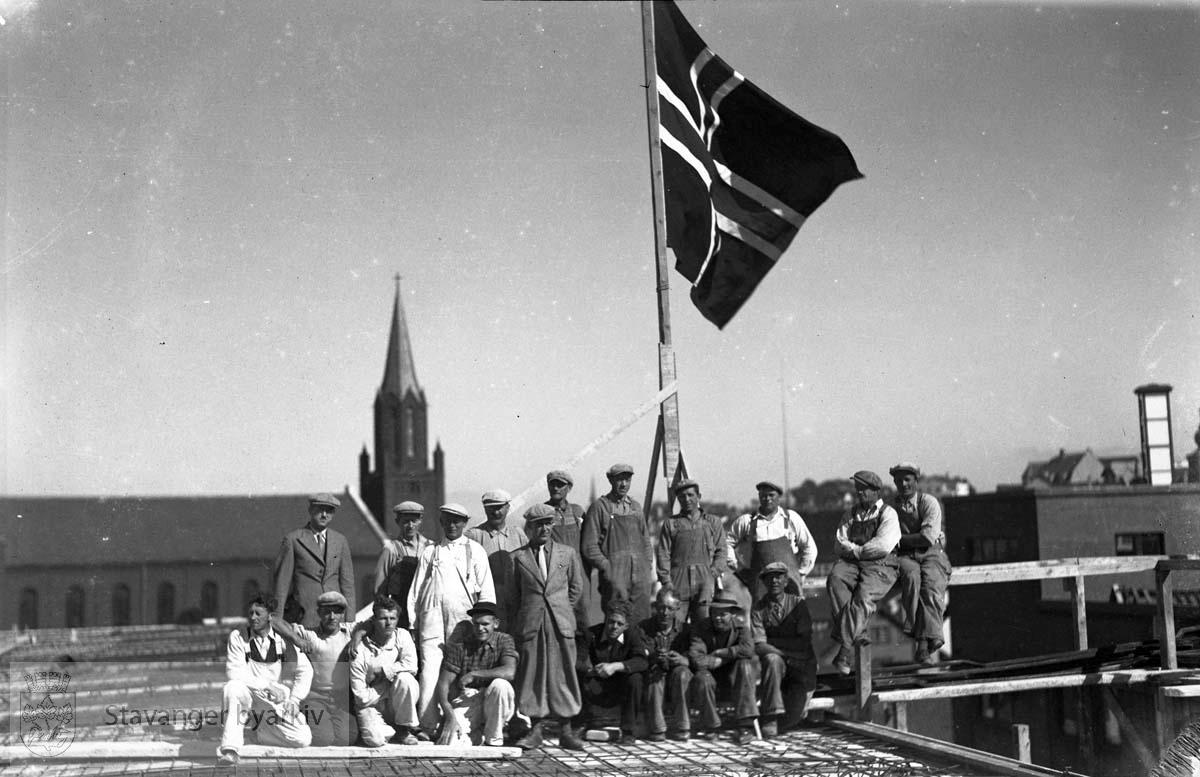 Trygdekassen under oppføring.Sperreflagg på taket.Arbeidergruppe Petrikirka i bakgrunnen
