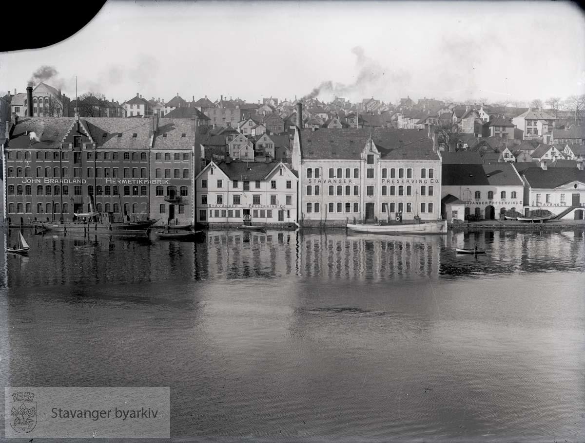 Til venstre John Braadland Hermetikfabrik. Resten av bygningene tilhører Stavanger Preserving Co., også den gamle tollboden helt til høyre. Braadland har nettopp utvidet mot nord (1906)...Fabrikkeier John Braadlands båt, Victoria liggende til venstre i bildet. Bygget i Chatham, 1895, kjøpt av Braadland i 1907.