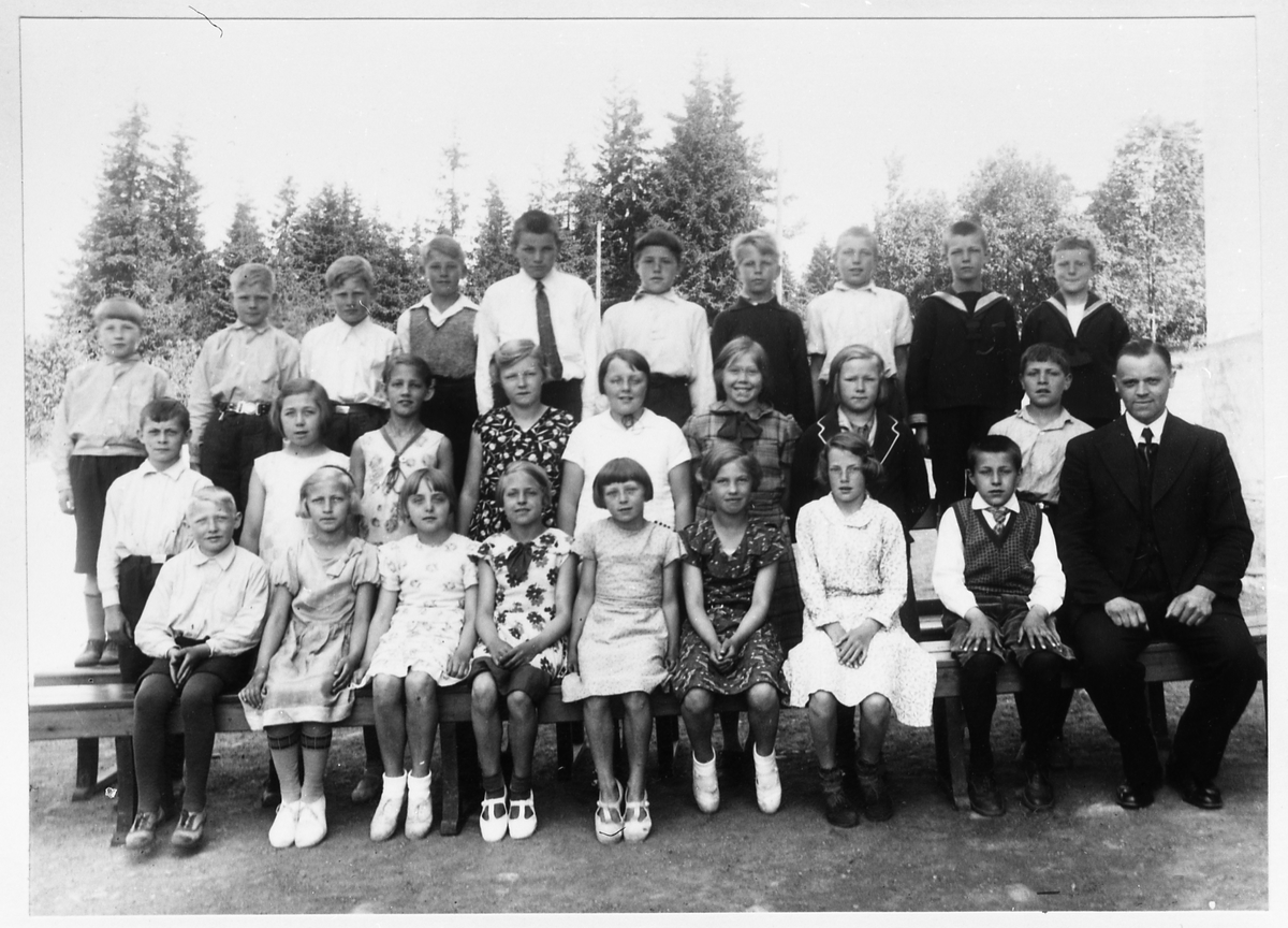ca563797 Avfotografert gruppebilde med barn og en voksen mann, trolig et skolebilde.  Hverken personer eller