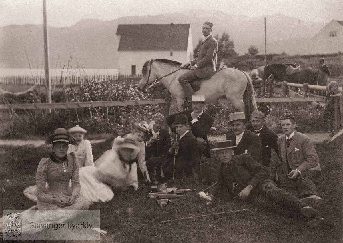 Picnic i gresset. Mann til hest i midten. Hus og hage foran fjorden i bakgrunnen.