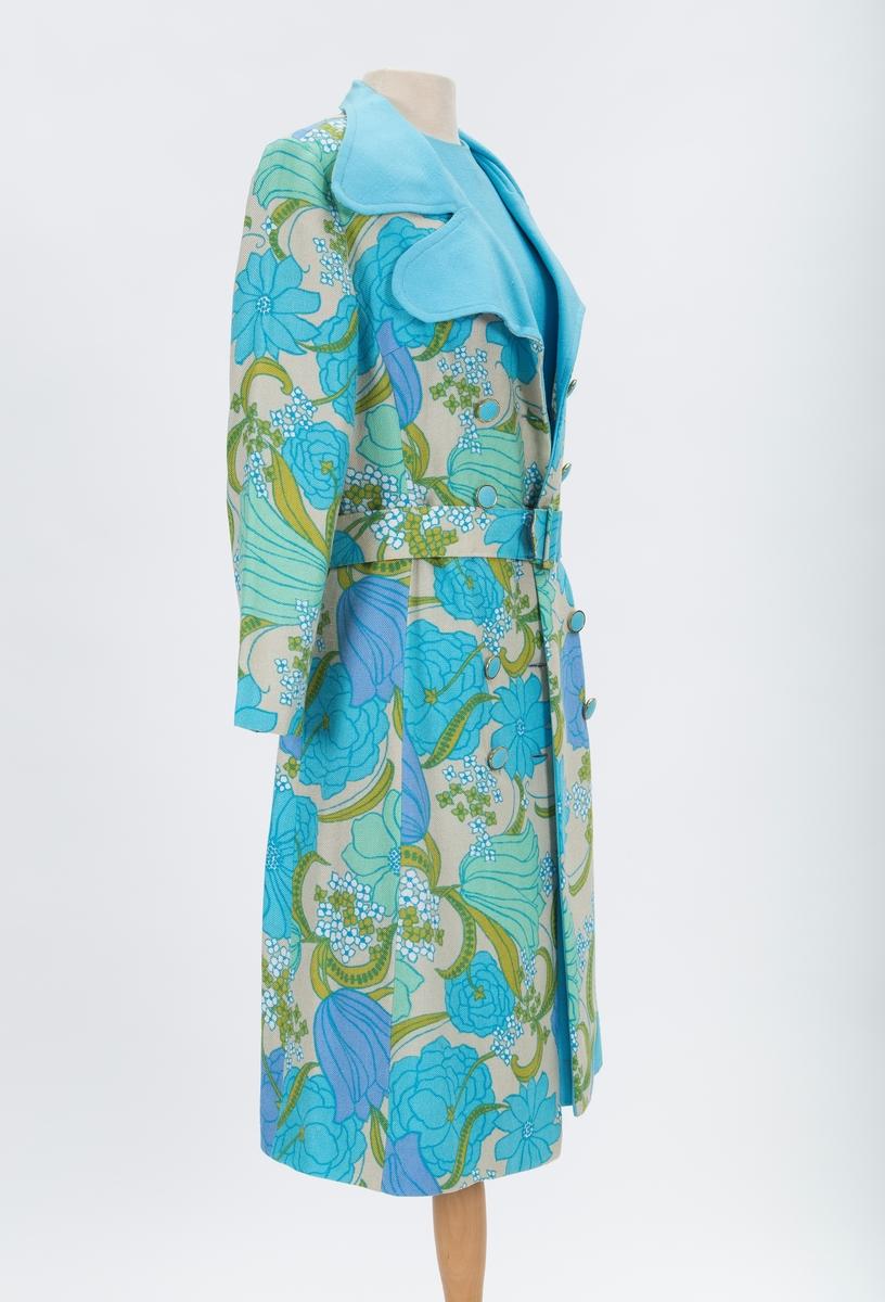 Festantrekk bestående av kåpe og kjole. Ermeløs kjole Innsvinget i livet med innfelt mønstret stykke. Rund halslinning, glidelås bak. Dobbeltspent kåpe med brede slag, krage , belte.
