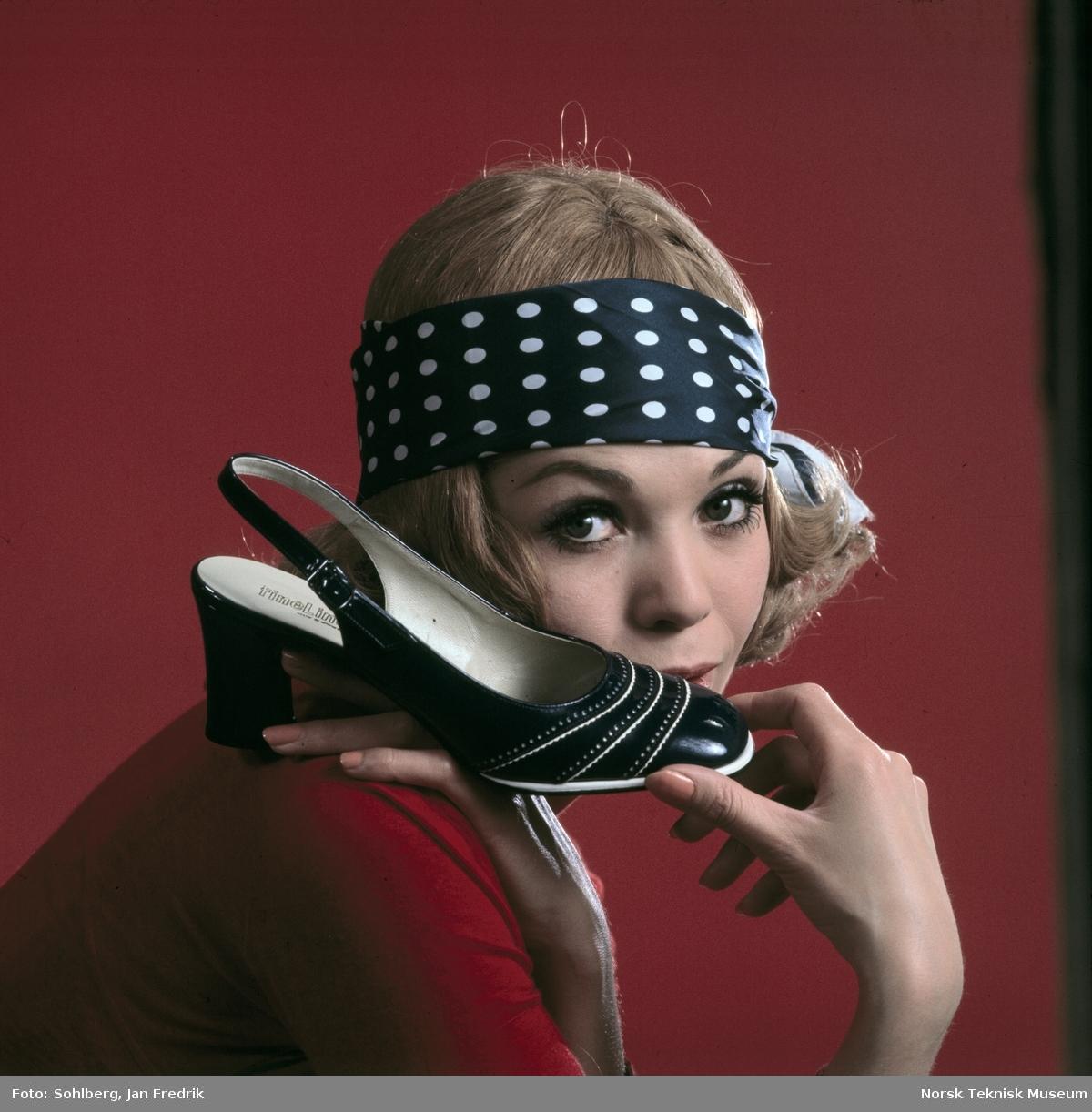 Tidlig norsk reklame- / motefoto. En kvinnelig modell holder opp enblå sko med hvite striper og høy hæl, hun virker fornøyd med tidens skomote. Hun har et blått hårbånd med hvite prikker. Rød bakgrunn.