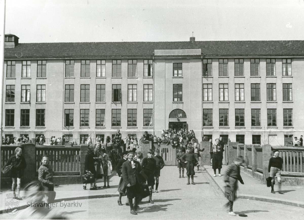 Fasade med skolegård og skolebarn.