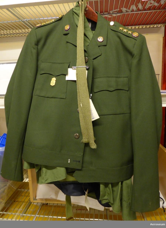 """En komplett kaptensuniform från svenska armén. Troligtvis från tekniska kåren. Består av en grön tygslips med slipshållare i metall, ett par gröna byxor och grönt skärp, en grön skjorta, en grön jacka, och en grön kaptensmössa. Skjortan är storlek 39, jackan är storlek C 50, och byxorna är storlek C 52.  Det finns en datummärkning i kaptensmössan: """"1969"""", och en i jackan: """"1971"""". I en innerficka i jackan sitter det 2 bläckpennor och en stiftpenna. På skjortans och jackans axlar sitter det tre stjärnor och ett antal kugghjulsymboler. På jackan sitter även ett tjänstgöringstecken från """"Arméns tekniska centrum"""". På kaptensmössan sitter ett metallmärke som visar att det var armén (två svärd som korsar varandra). Innuti kaptensmössan finns namnet """"Christer Lagert"""" och två olika adresser."""