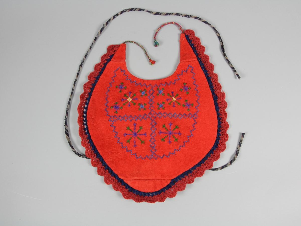 Bröstlapp med framsida av rött ylle. Något oregelbunden rund form med uttag för halsen. Knyts i nacken med två tvinnade snoddarna som avsluttas med en kort knuten toffs. Framsidans tyg är skarvat på tre ställen. Mitt på bröstlappens framsida är ett broderi i korstygn med mönster av stjärnor eller snöflingor. Broderiet är utfört i grönt, lila, grått och blått ullgarn. Runt ytterkanten på lappen är en spets virkad i två delar. Den inre med mörkblått ullgarn och den yttre uddkanten med rödbrunt ullgarn. Fodertyget på baksidan är ett kypertvävt styg som bär rester av lila färg. Fodret är skarvat på ett ställe. Möjligen är denna söm gjord på symaskin. I övrigt är plagget sytt för hand med lintråd. På baksidans nederkant finns en kort och en lång snodd av randigt bomullstyg att knyta bakom ryggen.