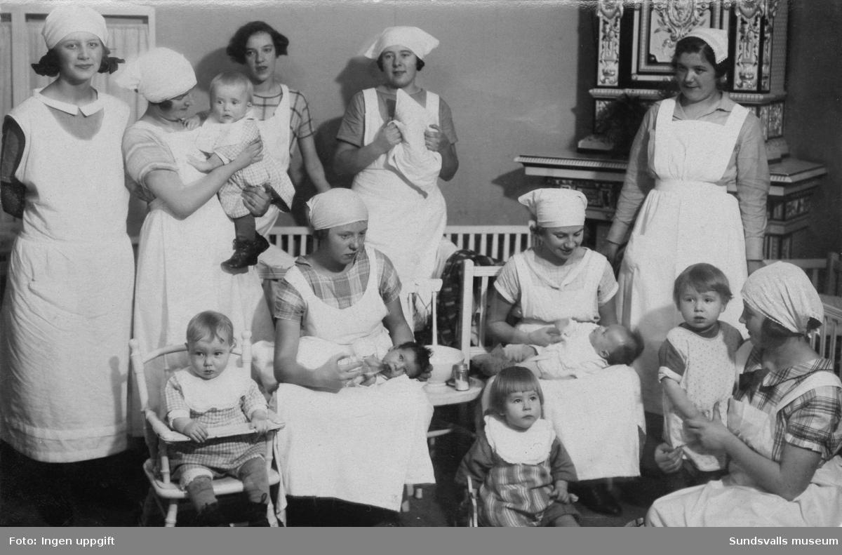Gruppbild med elever samt barn från spädbarnshemmet, vid Vita Bandets barnsköterskeutbildning. Lärarinnan stående till höger heter Ingrid Erland. Vita Bandet huserade vid denna tidpunkt i en lägenhet i Thuressonska huset vid Nytorget. Först 1928 införskaffades en egen fastighet på Tjärngatan 4.