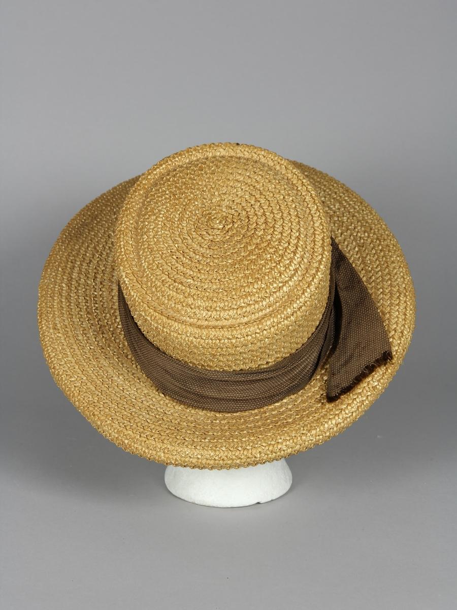 Stråhatt av flätat ståband. Med ett asymetriskt monterat hattband i brunt med tunna ljusa linjer. Hattens brätte är bredare framtill än baktill. Brättet har en svagt klockad form. Kullen är oval och med flat avslutning.