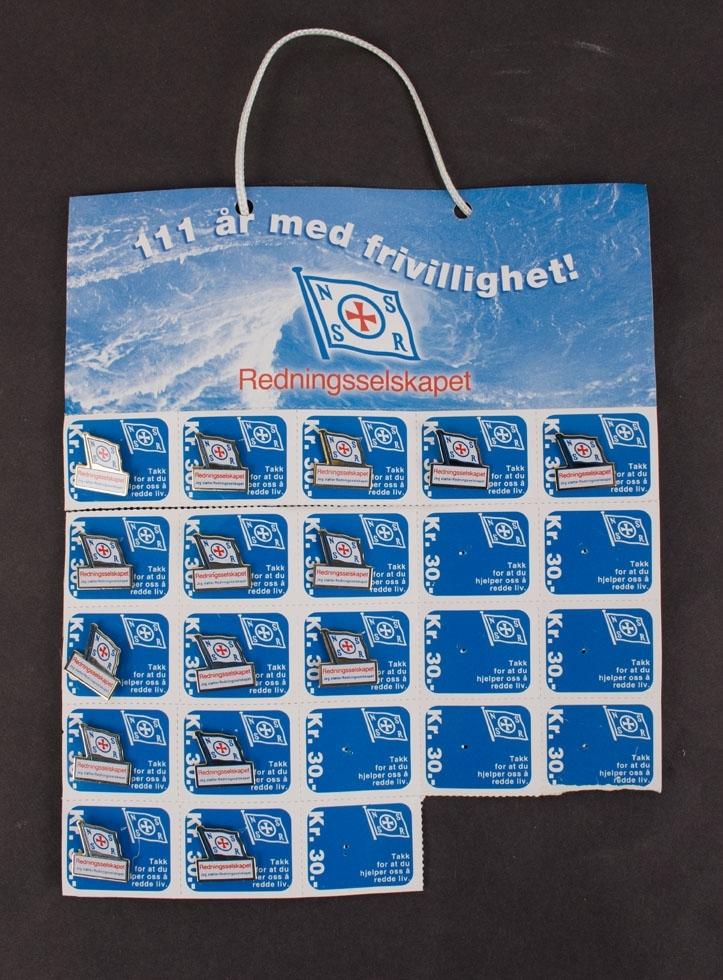 Pins. Ark/brett med jakkemerker for Redningsselskapets (Norsk Selskab til Skibbrudnes Redning). Brettet består av til sammen 15 stk. emaljerte merker og har snor øverst slik at selger kan ha det rundt halsen.