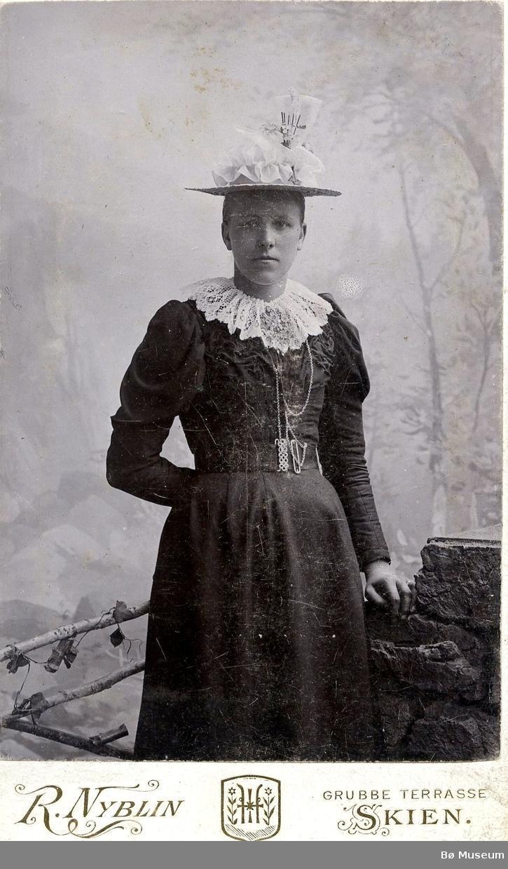 Atelierfoto av ei ukjent kvinne i byklær.