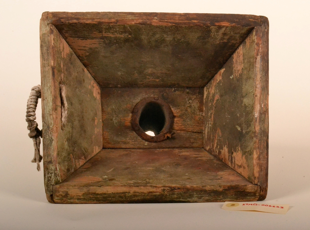 Trakt bestående av rektangulær trekasse. KAssen avsmalner mot botn.  Avløpet er et rundt rør i midten på botn av kassen. Avløp er et rør i metall. Røret har en fals som er spikret til utvendig botn av kassen.  Trakta har et håndtak, plassert utvendig øverst  ved kanten. Håndtaket er trolig hempe til oppheng.