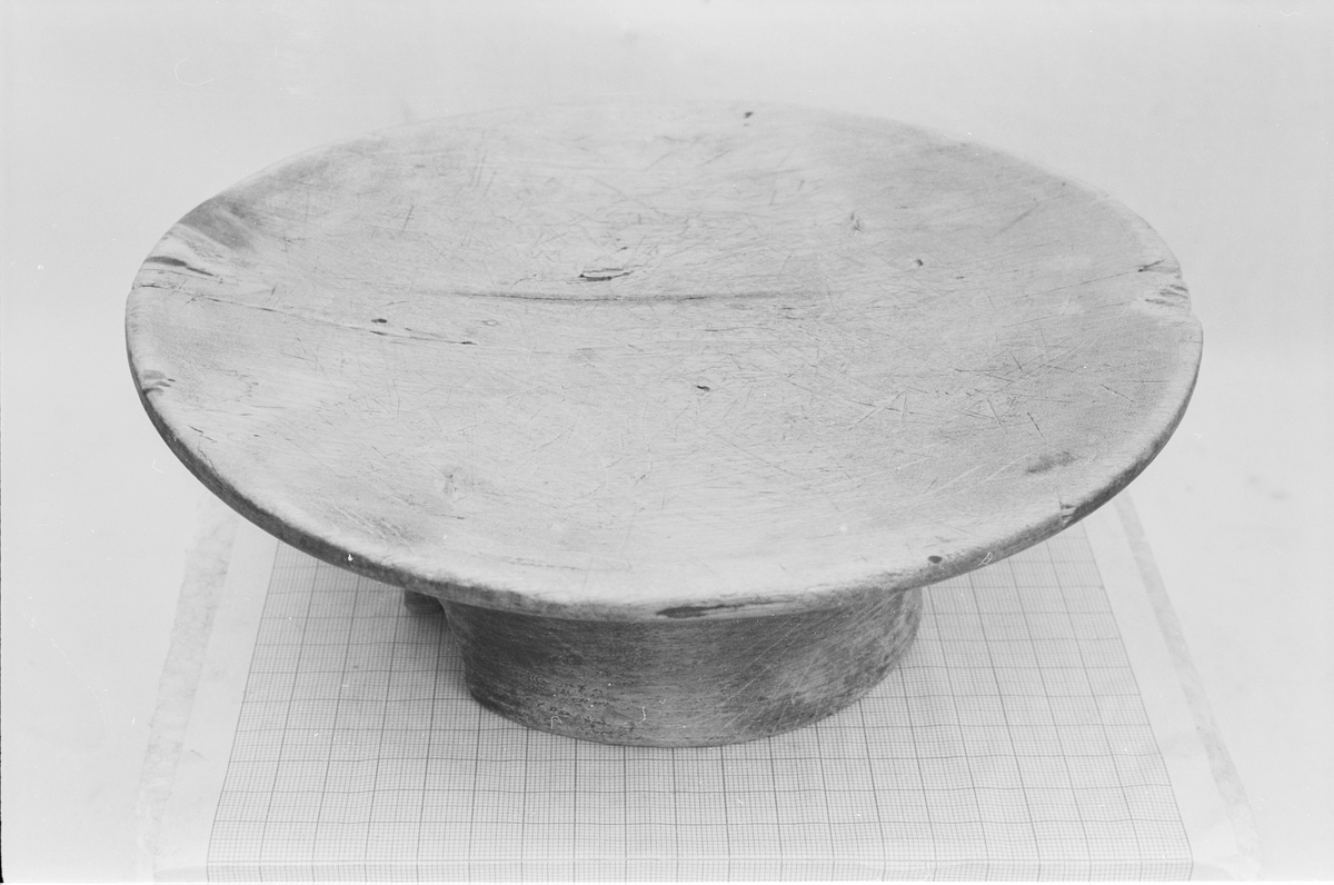 Rundt fat på stett med en svak fordjupning. På undersida er det skåret et mønster (en enkel geometrisk bord)