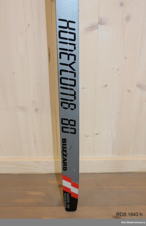 Flat ski med svært liten bue. Bøy uten tupp. Svakt avfaset bakende, litt oppbøyd. Rottefella binding (rød). Åttekanta hælstøtte. Avsmalende fra midten mot begge ender.  Stempel og klistremerker på skiet etter VM.