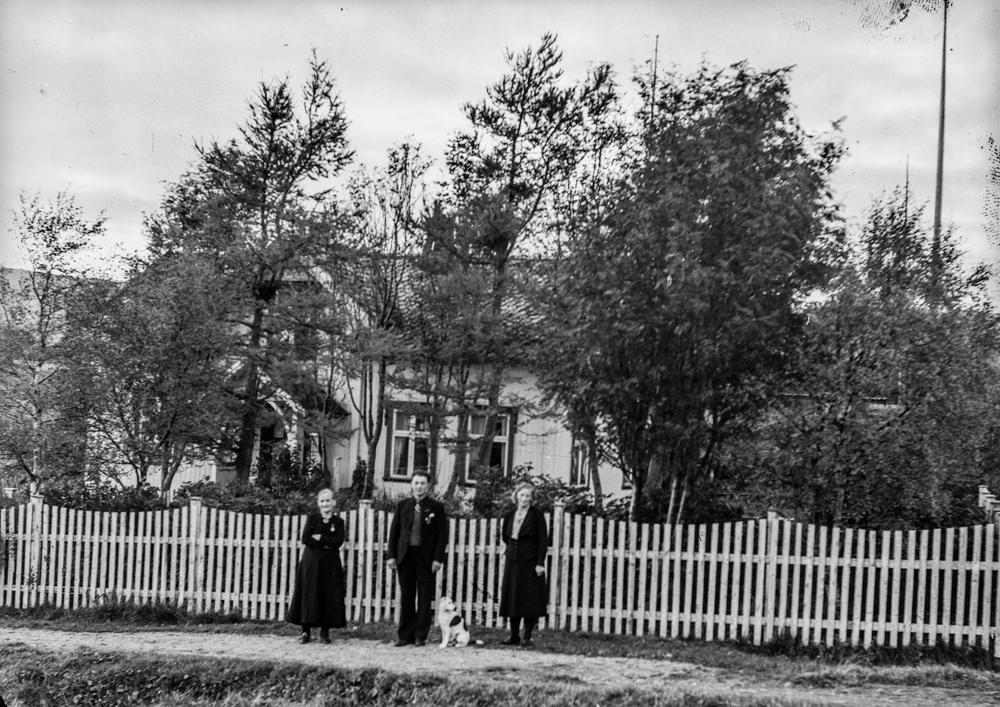 Leirfjord, Leland, Breivika. F.v.: Marie Leland, Julius Leland, med hund og Ragna Leland foran huset i Breivika, med stakittgjerde foran.