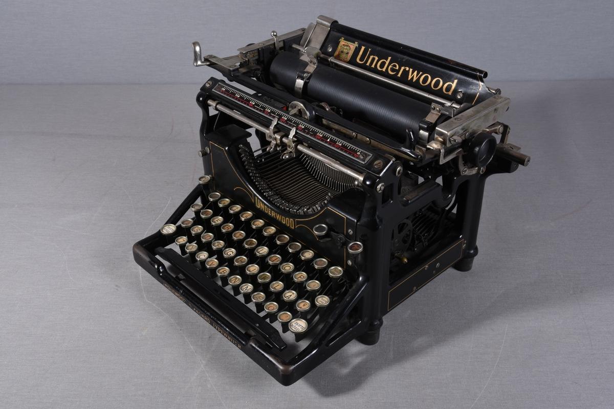 Manuell skrivemaskin med sideveis bevegelig papirvalse. Åpent tastatur.