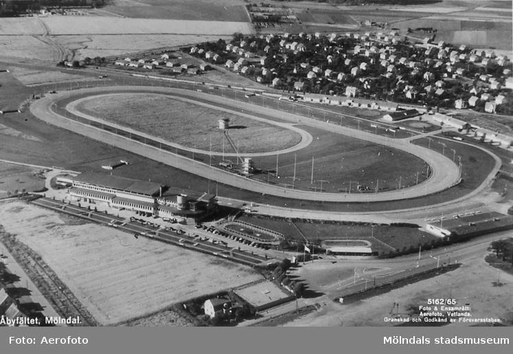 Flygfotografi över Åby travbana i Åby, Mölndal, på 1950-talet. I bakgrunden ses bebyggelse på Solängen. Västra Solängen, som byggdes 1956-1965, finns med på bilden. Avfotograferat vykort. AF 3:6.