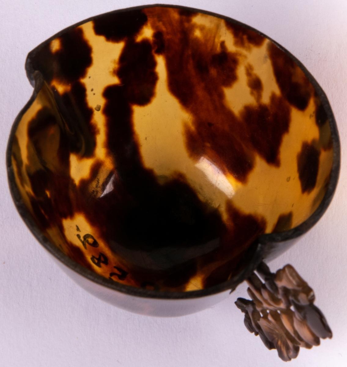 Kopp av sköldpadd, ena halvan något vidare än den andra. Sidohandtag i genombruten utskärning, växtornamentik.