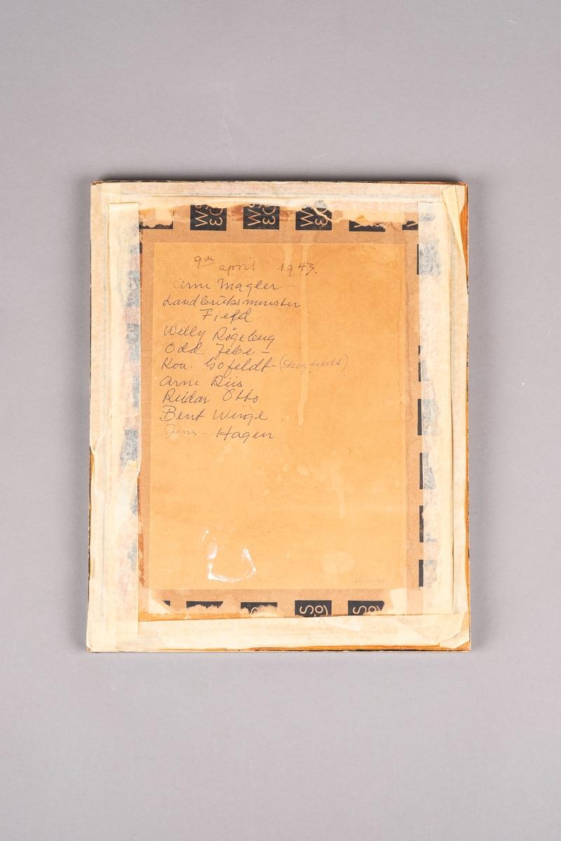 Innrammet bursdagskort. Det er skrevet dikt på kortet, og er signert av 9 medfanger. Nederst ved høyre hjørne er det tegnet et segl. Rammen er av tre med glassplate.