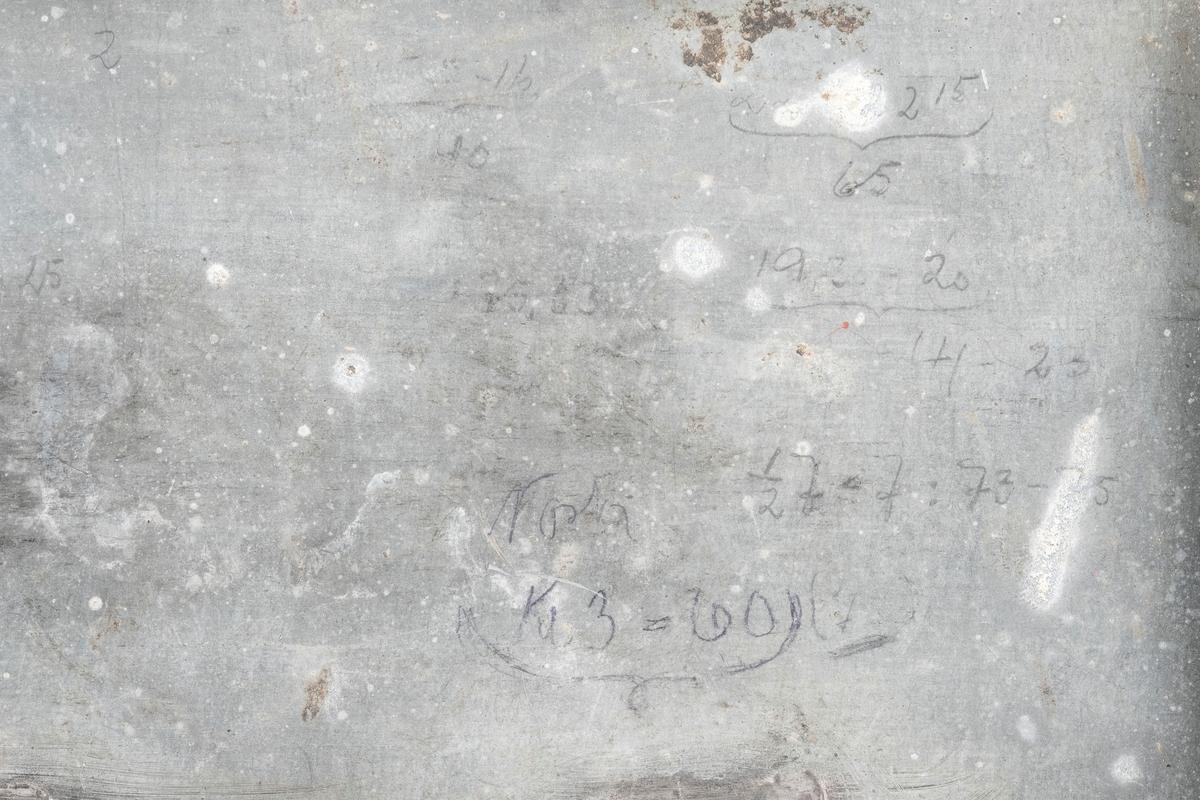 Blikkboks for oppbevaring. Lokket lukkes med hengsler som kan låses med hengelås. På lokket det er håndtak. På innsiden av lokket er det påført noe tall, ser ut som et regnestykke. På baksiden av blikkboksen er det påført tekst, noe av det er uleselig.