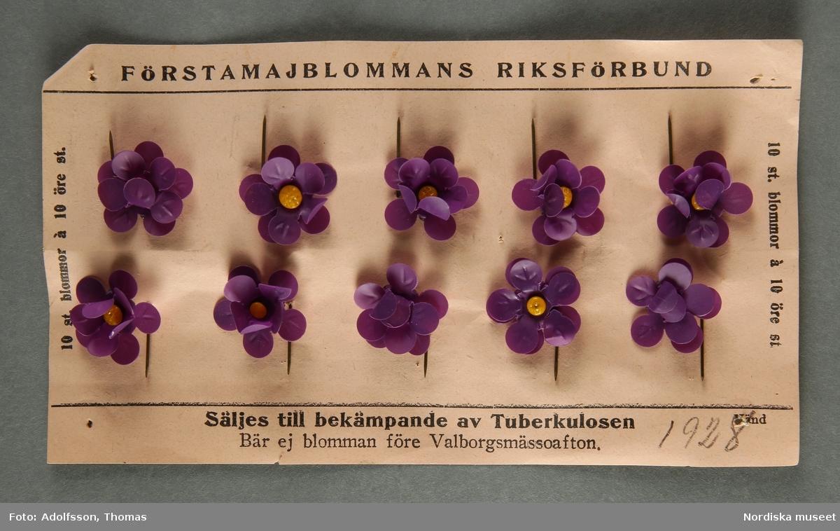 """Majblomskarta med 1928 års majblommor. Beige karta av rektangulärt papper med tryckt text """"FÖRSTAMAJBLOMMANS RIKSFÖRBUND. Säljes till bekämpande av Tuberkulosen. Bär ej blomman före Valborgsmässoafton10 st. blommor à 10 öre."""" Handskrivet i blyerts på framsidan av kartan """"1928"""". På kartan fästa 10 st majblommor av celluloid med dubbla kronblad i mörklila med gul mittknopp av glas och nål av gulmetall. På baksidan tryckt text: """" """"Utdrag ur Förstamajblommans Riksförbunds stadgar."""" + hela pararapraf 2 och 5. Lena Kättström Höök/ 2013-04-22  Vid försäljningen var majblommorna fästade på detta sätt. /Lena Kättström Höök 2008-11-17"""