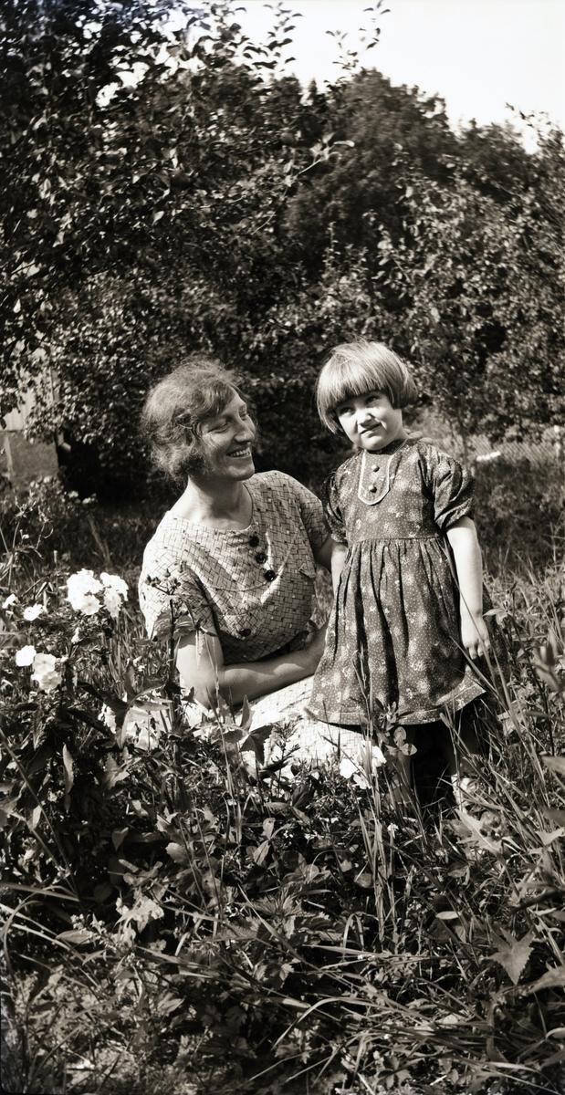 f83a894920e6 Alma Rosengren sitter i trädgården med en flicka vid en blommande flox.